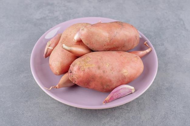 보라색 접시에 마늘을 넣은 요리하지 않은 감자.