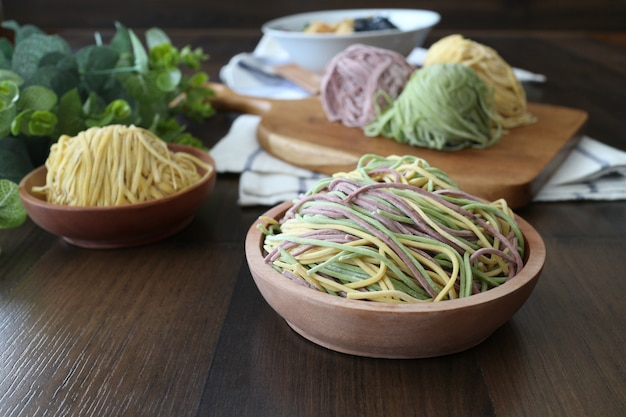 Uncooked rainbow noodles on the wooden bowl