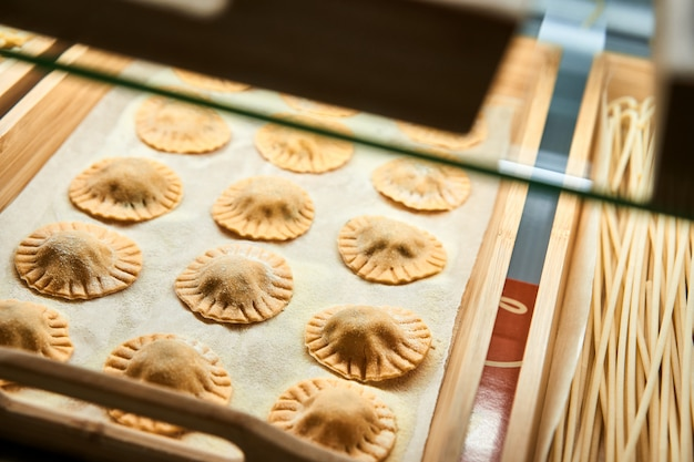Uncooked ravioli mix on wooden tray in the shop window.