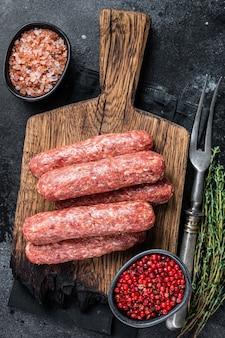 Сырые сырые сосиски кебаб из говядины и баранины на деревянной доске. черный фон. вид сверху.