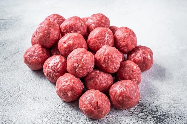 Сырые сырые фрикадельки из говядины и свинины со специями на кухонном столе. белый фон. вид сверху.