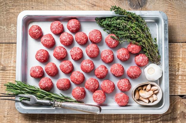 Сырые фрикадельки из сырой говядины и свинины с тимьяном и розмарином на кухонном подносе. деревянный фон. вид сверху.