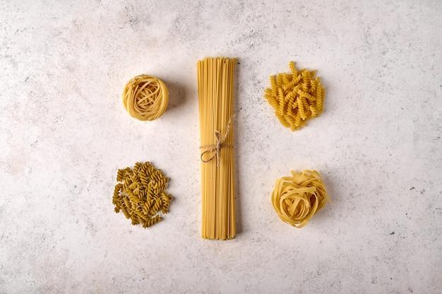 Сырые сырые пучки спагетти, феттучини, жирандоле и тальятелле на сером текстурированном фоне