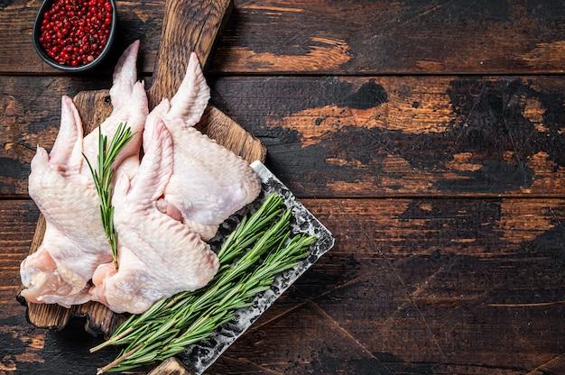 未調理の生の手羽先肉切り包丁を備えた食肉処理場の鶏肉。暗い木の背景。上面図。スペースをコピーします。