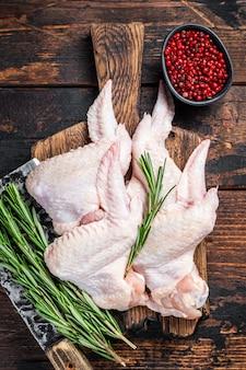 未調理の生の手羽先肉切り包丁を備えた食肉処理場の鶏肉。暗い木の背景。上面図。