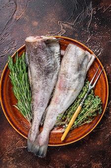 Сырая сырая треска или треска в деревенской тарелке с травами и вилкой