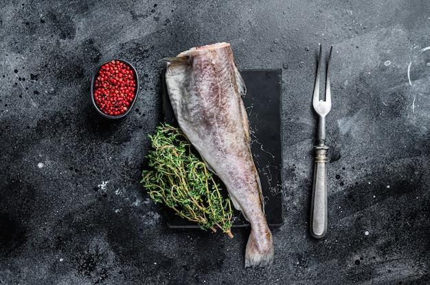 Сырая рыба сырая треска целая на мраморной доске с тимьяном. черный фон. вид сверху.