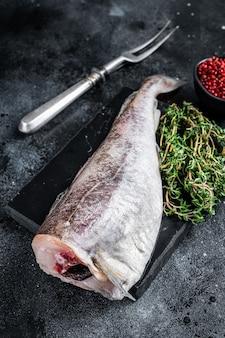 Сырая сырая целая рыба трески на мраморной доске с тимьяном