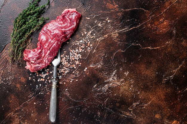 Uncooked raw flank beef steak on meat fork