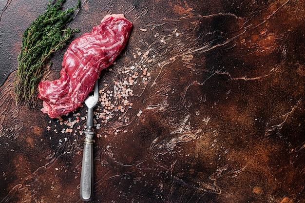 Сырой стейк из сырой говядины на вилке для мяса