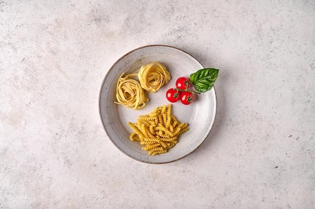 Сырые сырые помидоры черри girandole tagliatelle и базилик на белой тарелке на серой текстуре