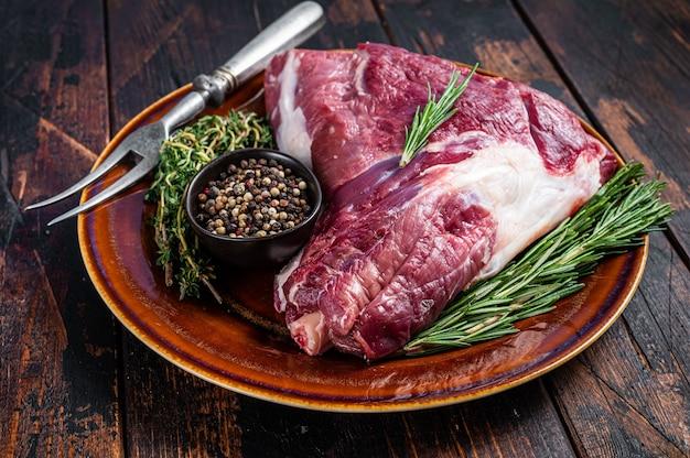 素朴なプレートにローズマリーとタイムを添えた未調理の生の山羊の太ももまたは脚。ダークウッドのテーブル。上面図。