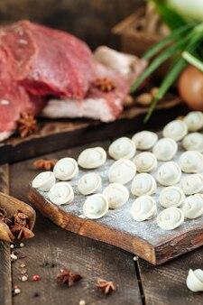 ダークウッドの肉に牛肉と玉ねぎを小麦粉で調理した生の自家製餃子。ロシアの郷土料理ペリメニ。