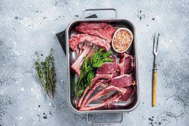 조리되지 않은 생 양고기, 강철 주방 트레이에 담긴 양고기 볶음. 회색 배경입니다. 평면도.