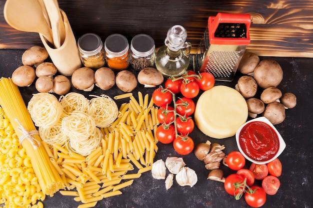 新鮮で健康的な野菜、さまざまなスパイス、ひまわり油の横にある未調理の生マカロニ、パスタ、スパゲッティ、ダークヴィンテージの素朴な木製の背景