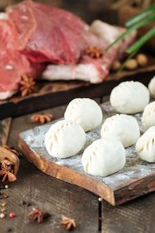Сырые сырые манты. среднеазиатские традиционные пельмени мясное блюдо с мясом и луком.
