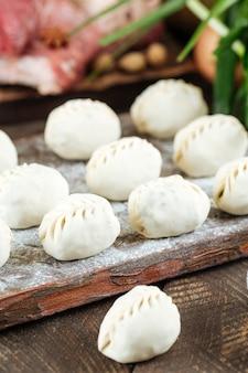 Сырые сырые манты. среднеазиатские традиционные пельмени мясное блюдо с мясом, лук jusai. неподготовленный