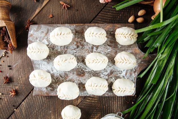 Сырые сырые манты. традиционное среднеазиатское пельмени с мясом и луком