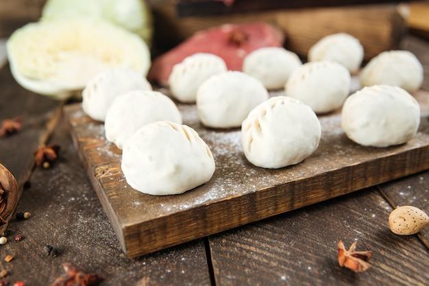 Сырые сырые манты. среднеазиатские традиционные пельмени мясное блюдо с мясом, картофелем и луком