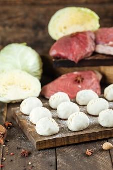 Сырые сырые манты. среднеазиатские традиционные вареники с мясом говядины и луком jusai на доске с мукой на темном дереве