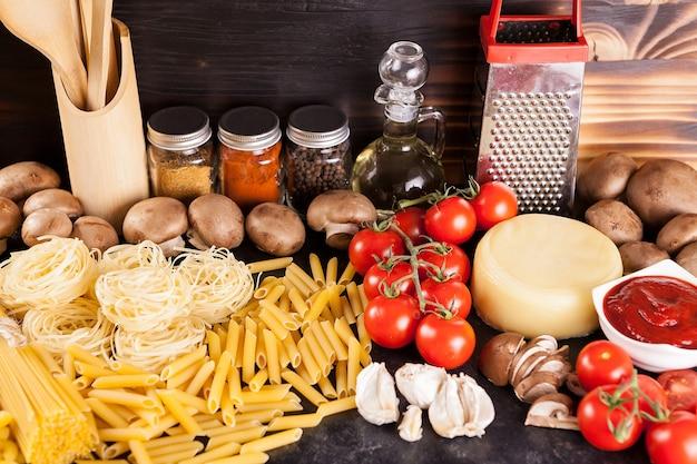 さまざまな野菜、スパイス、ひまわり油の横にある素朴な背景の未調理の生パスタ