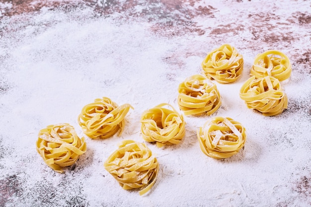 Uncooked raw pasta on wooden kitchen table.