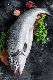 Сырой сырой морской лосось целая рыба на деревянной доске с травами. черный фон. вид сверху.