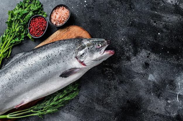 Сырой сырой морской лосось целая рыба на деревянной доске с зеленью