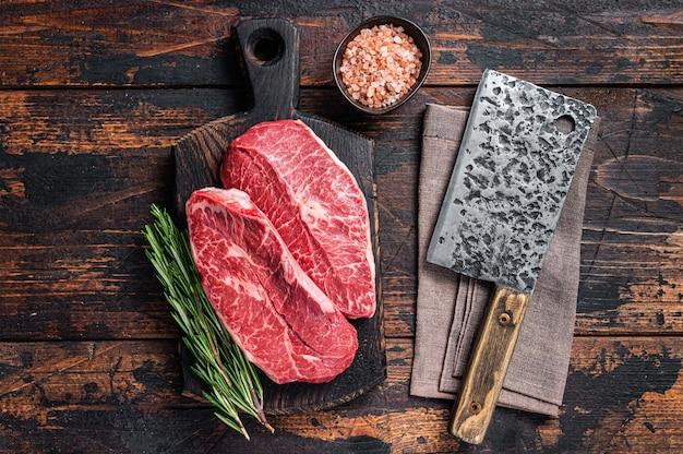 未調理の生のショルダートップブレードまたはフラットアイアンビーフミートステーキを、ミートクリーバー付きの木製肉屋ボードに載せます。ダークウッドのテーブル。上面図。