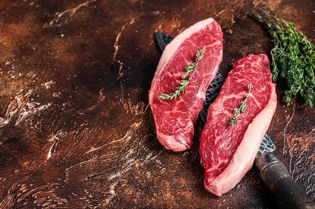 Необработанные сырые верхние части вырезки из вырезки или стейки из говяжьей крупы на нож для мясника. темный фон. вид сверху. скопируйте пространство.