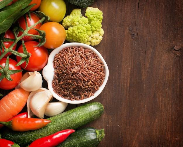 木の上に野菜とボウルに未調理の赤米