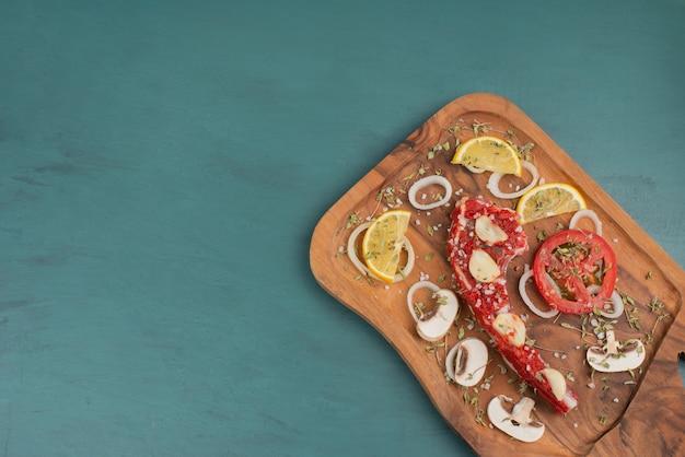 블루 테이블에 야채와 함께 생 쌀된 갈비 고기 조각.