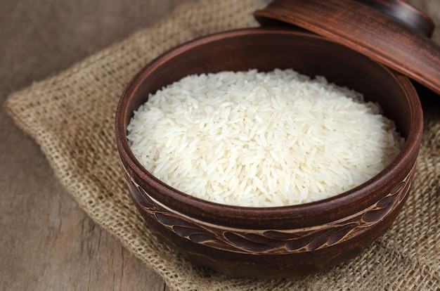 Uncooked rice in a clay bowl on wooden background