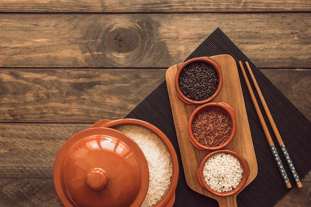 Uncooked rice grains pot with lid and bowl of rice on placemat with chopsticks
