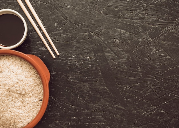 Uncooked rice grains with soya sauce bowl and chopsticks on textured backdrop