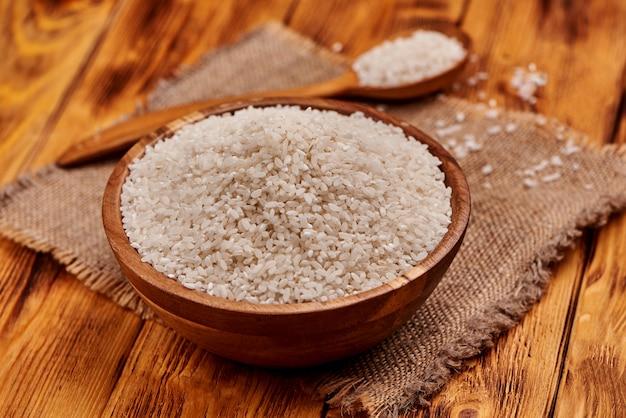 쌀, 소박한 배경 가득 나무 숟가락으로 나무 그릇에 생 쌀된 쌀. 확대.
