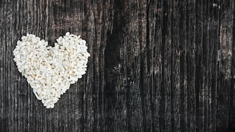 Uncooked rice made with heart on black wooden textured background
