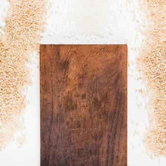 Uncooked rice with wooden chopping board