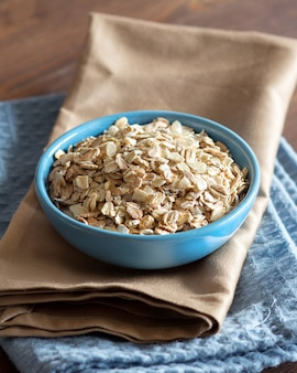 Uncooked rolled oats in a bowl on a napkin on a wooden table close up
