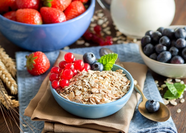 Uncooked rolled oats in a bowl with berries and milk on a napkin on a wooden table close up
