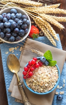 Uncooked rolled oats in a bowl with berries and milk on a napkin on a wooden table top view