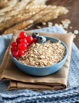 Uncooked rolled oats in a bowl with berries on a napkin on a wooden table close up