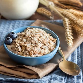 木製のテーブルにナプキンにベリーとミルクをボウルに生のオート麦をクローズアップ