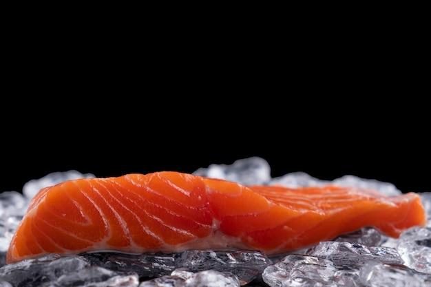 Сырое филе лосося во льду на темной поверхности