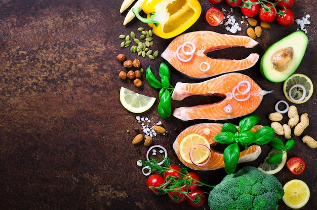 Uncooked salmon fish fillet with vegetables on wooden background.
