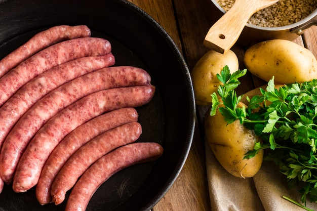 Uncooked sausages in iron cast pan, potatoes and fresh parsley