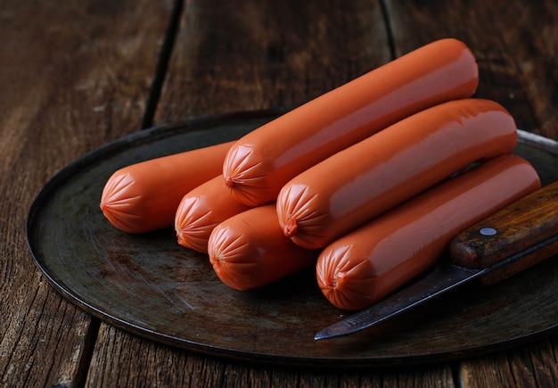 Сырые колбаски на деревянном фоне