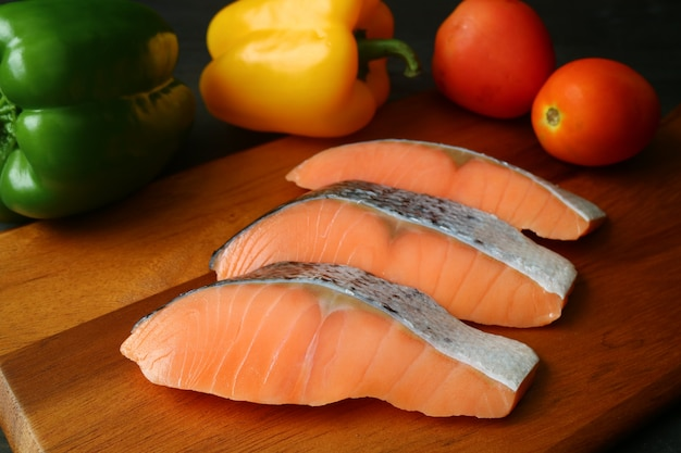 Uncooked sliced salmon on wooden cutting board with colorful vegetables