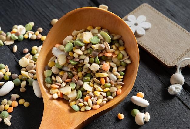 ガラスの瓶に大麦、スペルト小麦、エンドウ豆、豆、レンズ豆、ソラマメを入れたさまざまな色の混合マメ科植物の未調理のスープ