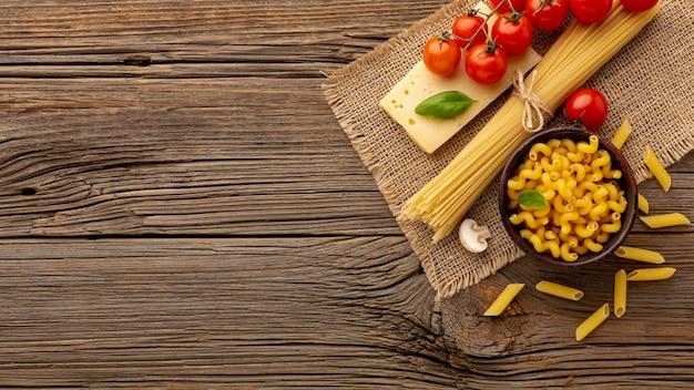 Сырые спагетти cellentani пенне помидоры и твердый сыр с копией пространства